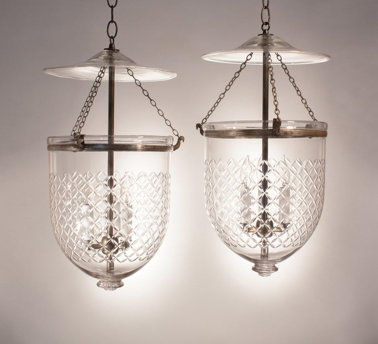 It's rare to find an authentic pair of 19th century English bell jar lanterns with such Fine quality hand blown glass that are so well matched. These circa 1870, medium-sized pendants are etched with a Waterford-style diamond motif and feature