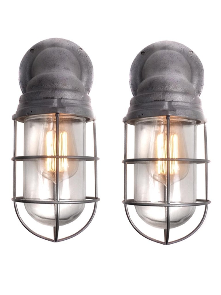 These are a nice matching pair of heavy cast Benjamin explosion proof sconces. They are original and complete with the screw in glass shade and outer cage.
