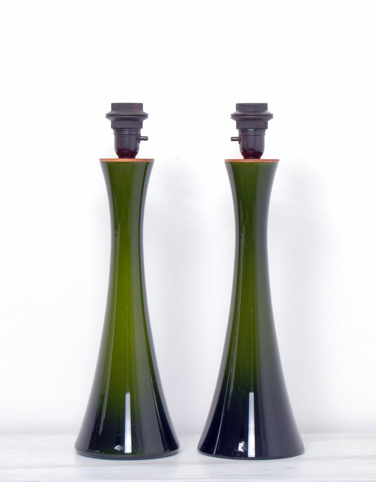 A pair of diabolo shaped Swedish green glass table lamps with teak fittings. Designed by Berndt Nordstedt for Bergboms. Newly rewired. For sale without the shades. The measurements and shipping costs stated are of the lamps without the shades.