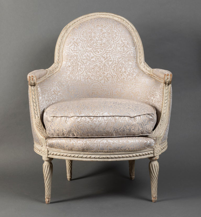 Beautiful pair of wing chairs in molded beech, richly carved and cream lacquered, decorated by banded moldings; enveloping armrest consoles with stylized acanthus leaves and rosettes; tapered legs with twisted grooves. DELANOIS stamp on the two