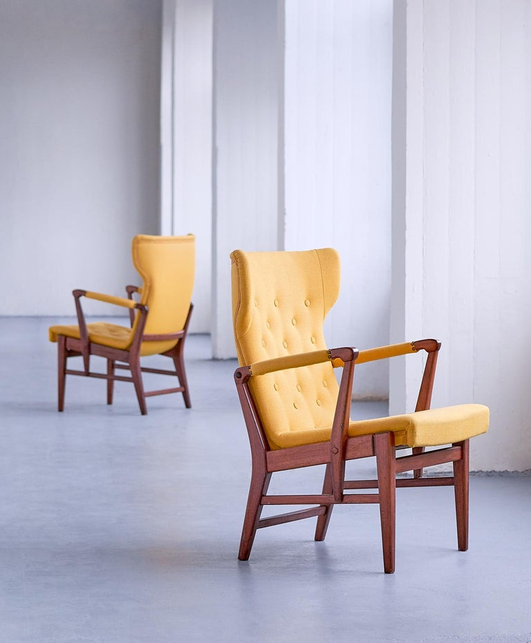 This rare pair of armchairs was designed by Bertil Söderberg and produced by Nordiska Kompaniet in Sweden in the 1940s. The elegant shape of the design is emphasized by the buttoned wing shaped back and seat. The mahogany frame is connected with
