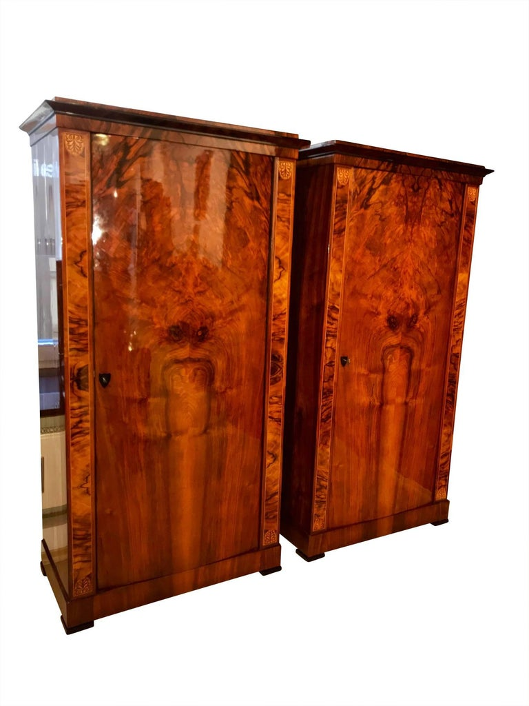 Beautiful Pair of one-doored Biedermeier armoires from Austria, circa 1830.  Wonderful lightly convex doors and amazing book-matched walnut veneer on the front and sides.   At the top of the lesenes, it has some nice maple inlays.  Finding armoires