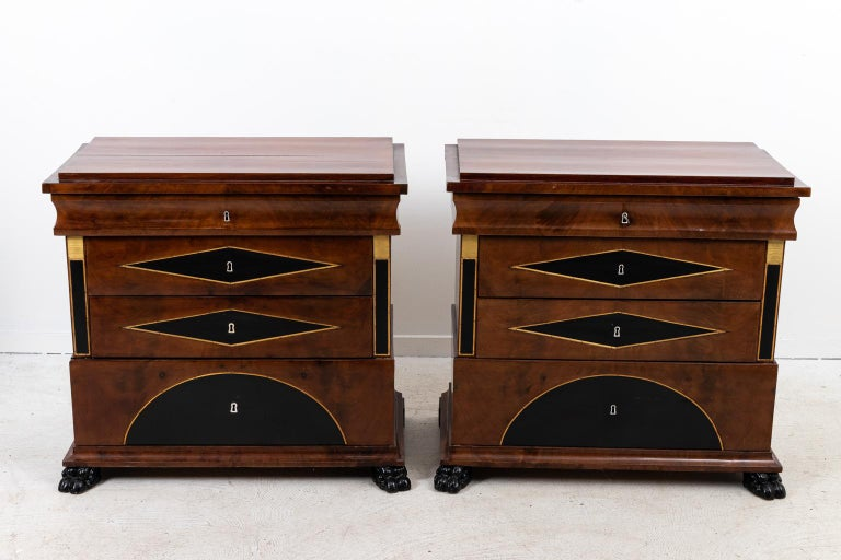 Pair of Biedermeier chests with brass inlay, three drawers, and French polish. Please note of wear consistent with age. The feet have been replaced.