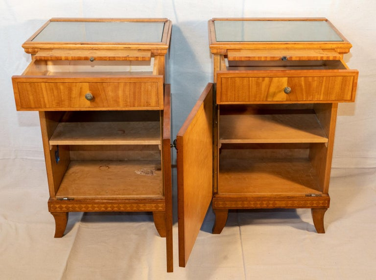 Pair of Biedermeier style nightstands, circa 1920. Art Deco Biedermeier style. Beautiful light wood with crossbanding and line inlays. Built very solid with good drawer construction and substantial vertical hinges. A matched pair. Different color