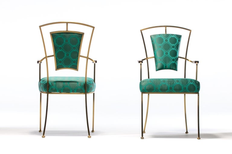 Sourced from a Beverly Hills estate and chic to the nines, this pair of 1960s Billy Haines style Hollywood Regency armchairs feature heavy duty solid brass frames with natural patina, walnut arm rests, and were professionally reupholstered in a Tony