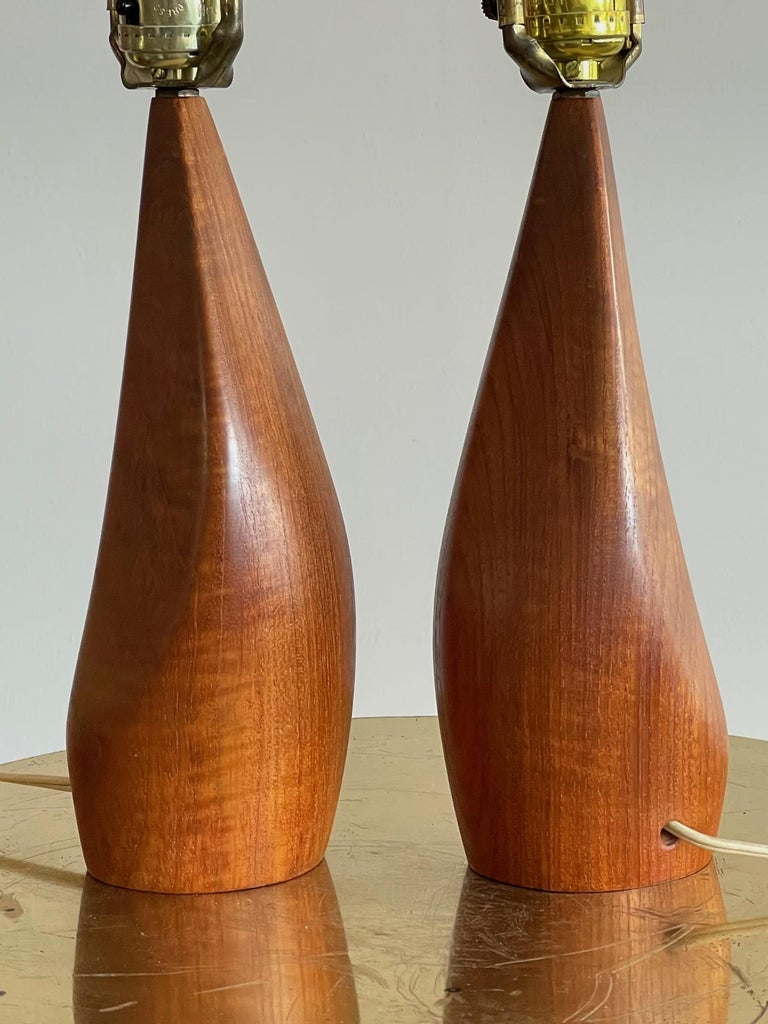 A pair of unusual Danish teak lamps by Ernst Henriksen, signed, circa 1960s. In very good condition with beautiful graining.