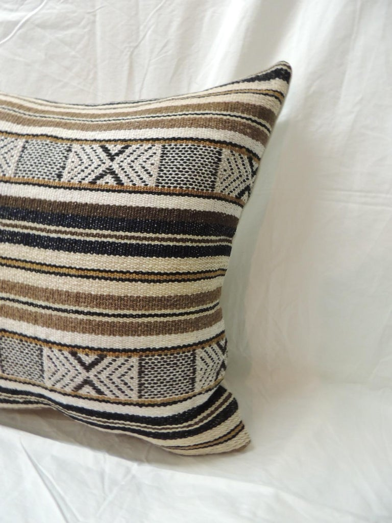 Pair of black and brown woven square decorative pillows with sand color linen backings.