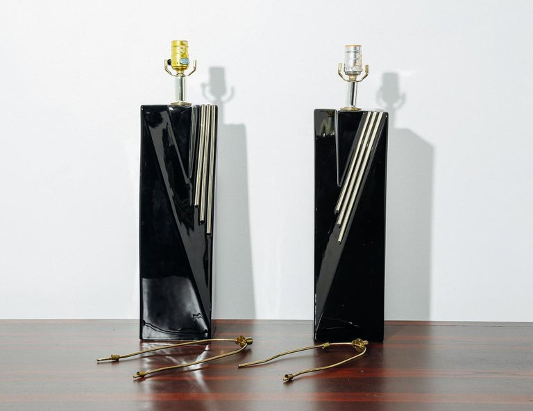 1980s table lamps with high gloss black ceramic bases and gold brass accents. No shades included.