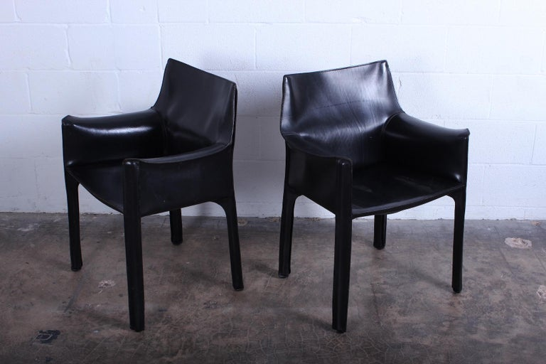 A pair of black leather cab armchairs designed by Mario Bellini for Cassina.