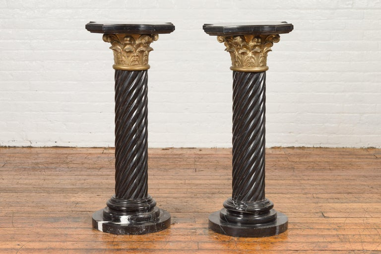 A pair of vintage Thai black Carrara marble pedestals with bronze Corinthian capitals and twisted columns. Created during the midcentury period, each of this pair of pedestals features a shaped marble top with in-curving effects, sitting above a