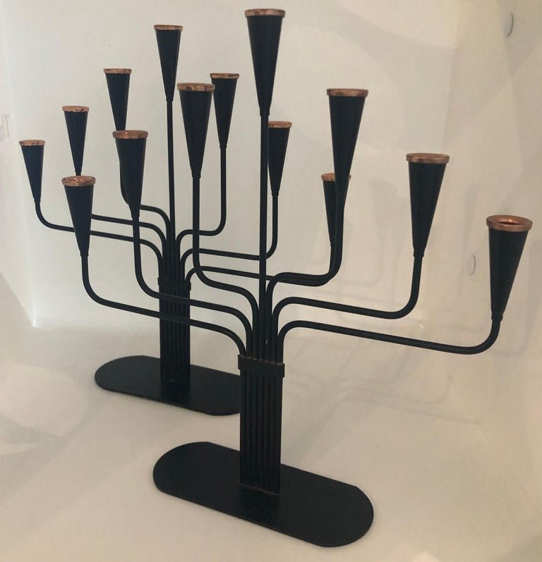Offered is a pair of pair of Gunnar Ander black enameled with bronze accents seven arm Ystad Metall 1970s candelabras. This chic yet refined pair of candelabras would look perfect on a dining table, fireplace mantel (fireplace), bar, bookcase and /