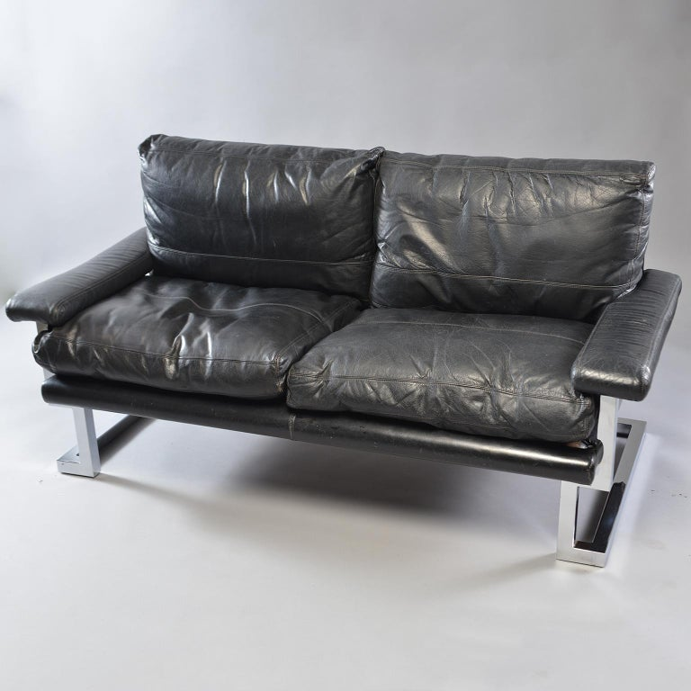 Pair of black leather and chrome sofas designed by Tim Bates for the Mandarin Collection of UK furniture maker Pieff & Co, circa 1970s. Comfortable with Classic midcentury lines and style. Padded arm rests, pebble finished leather and chromed steel