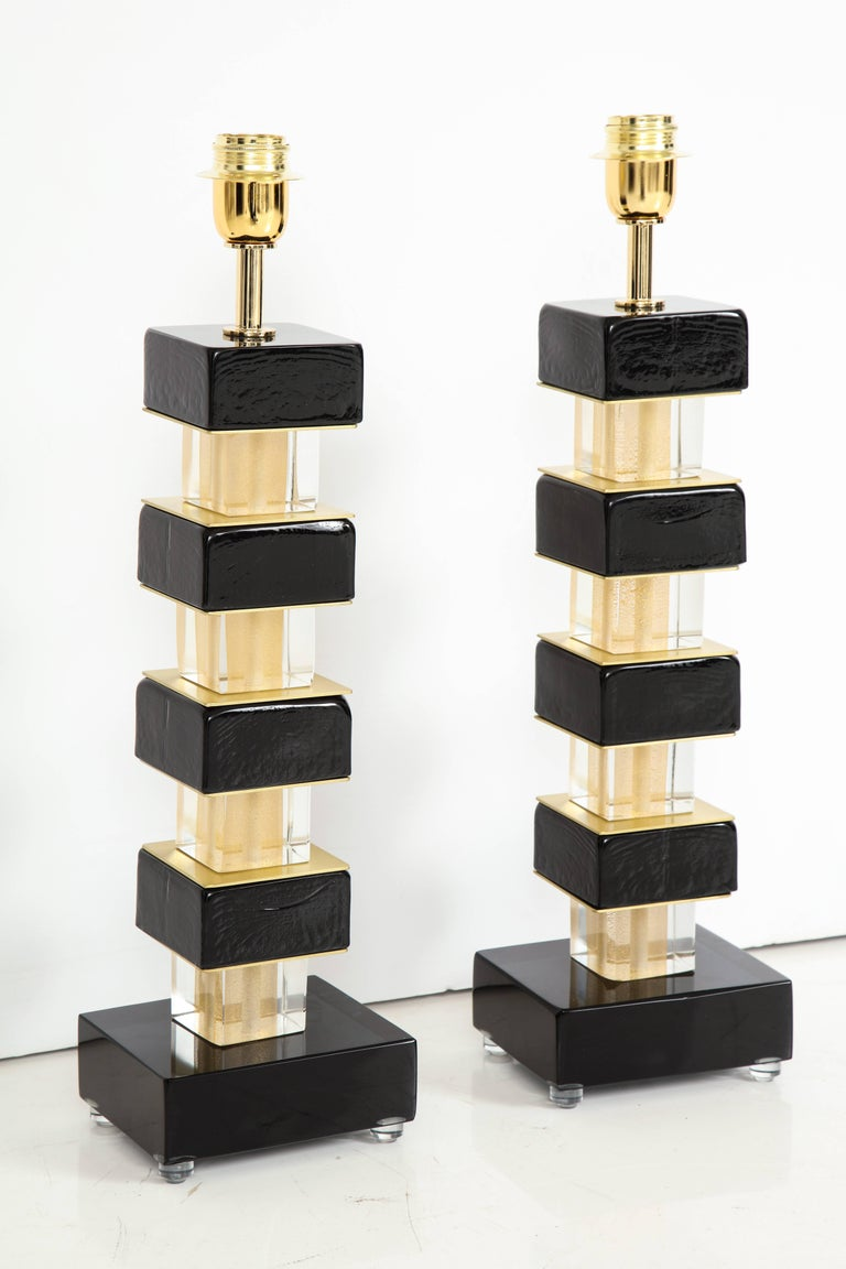 One of a kind pair of hand-casted and handcrafted black Murano glass and brass lamps. Individual glass blocks are separated by brass plates and sit atop a solid black Murano glass block base. Signed by the Murano Glass master himself, Alberto Dona.