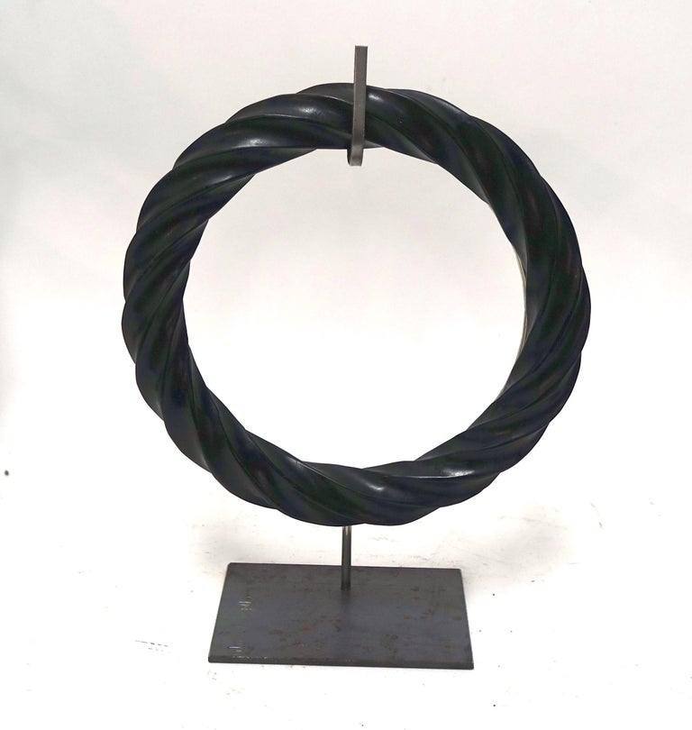 Contemporary Chinese pair of black twisted marble rings on steel stands. Honed finish. 10