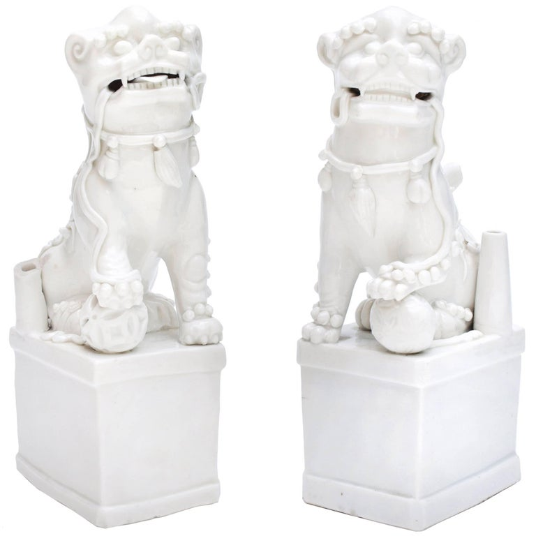 A pair of late 17th-early 18th century Buddhistic lions. Two males, of left and right pairing each sitting on a rectangular plinth with a wish granting ball under one paw and a ribbon in their jaws. Finished with an incense holder at the back and a