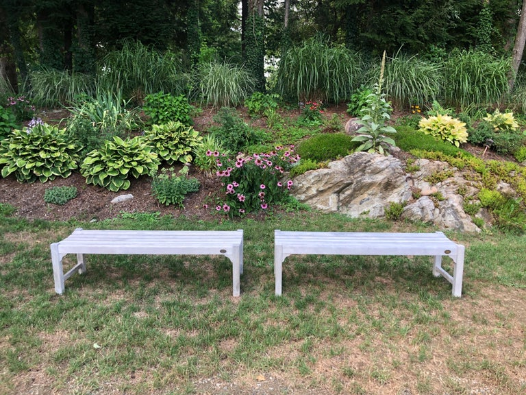 Pair of bleached outdoor teak benches. Perfect for the patio, garden or poolside. Solid teak with some outdoor wear. Sold as a pair only. Manufactured by Outdoor Designs Limited of Waterbury CT which has closed its business.