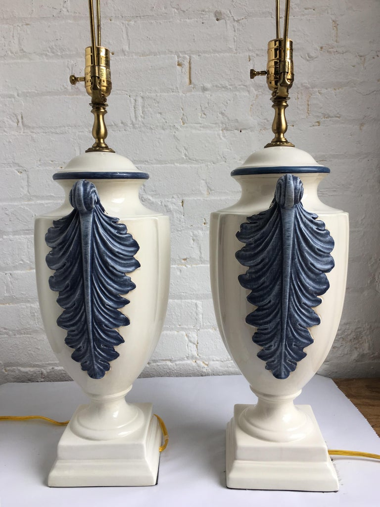 Pair of Hollywood Regency style blue and white porcelain glazed urn table lamps on plinth bases. Side handles feature dimensional hand painted plume or feather decorations. Lamp shades not included.   Measures: 31.5 inches high to harp. 22.5 inches