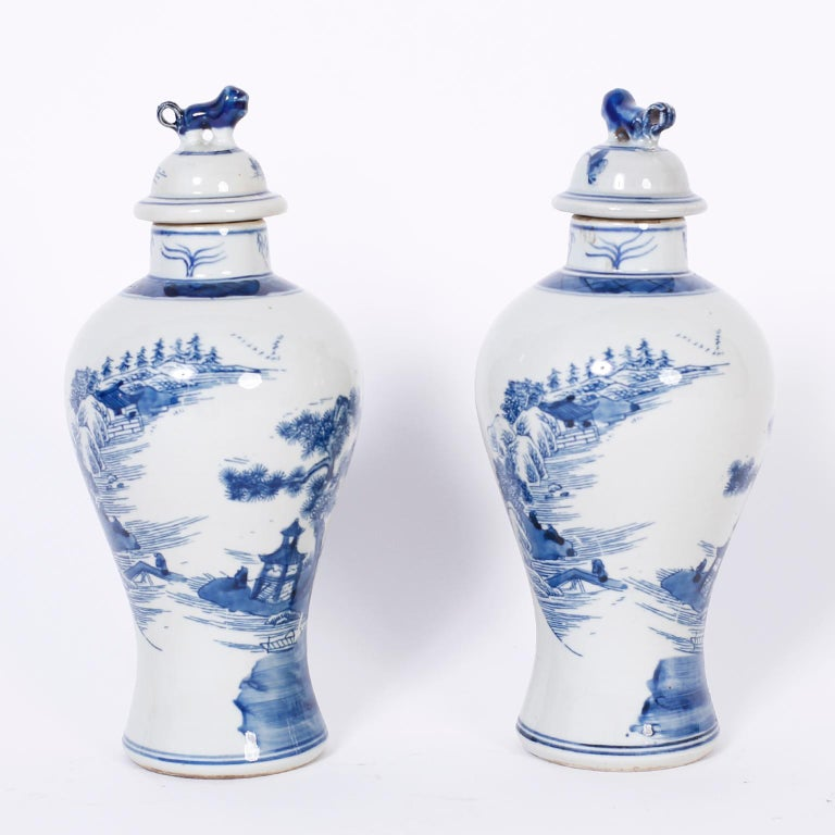 Pair of Chinese blue and white porcelain jars with foo dog handles and hand decorated with architectural landscapes all around.