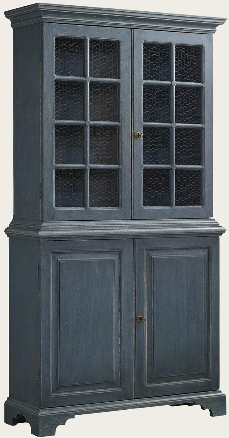 Beautiful pair of blue painted, Gustavian style Bookcases with charming chicken wire in the cabinet doors. The distressed patina has been expertly done and gives an unparalleled warmth. These hand-painted and hand-carved bookcases are wonderful