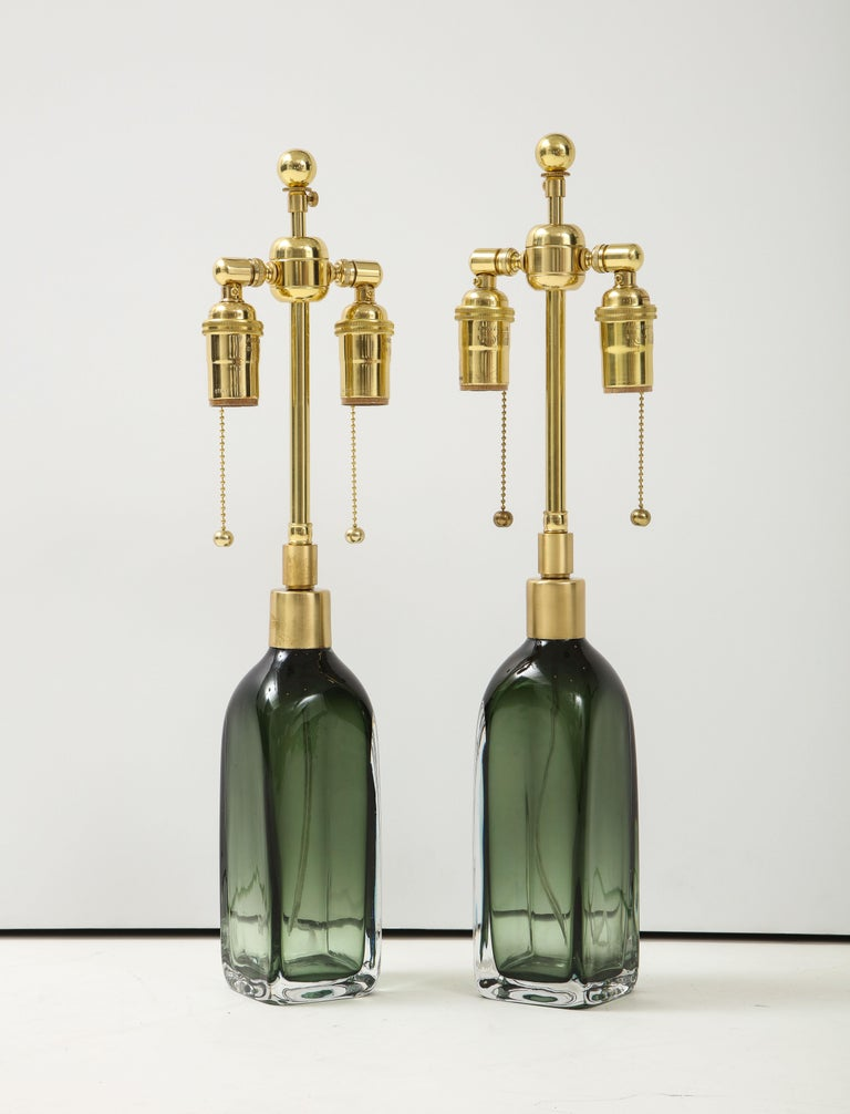 Pair of bottle green crystal glass lamps by Nils Landberg for Orrefors. The lamps have been newly rewired with adjustable polished brass double  clusters that take standard light bulbs. One of the glass bodies is slight taller than the other but