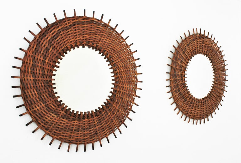 Beautiful pair of woven rattan circular mirrors with straight rays endings as sunburst mirrors, Spain, 1960s. The thick woven frame surrounding the glass highlight the beauty of this pair of wall mirrors. They will add a fresh accent wherever you