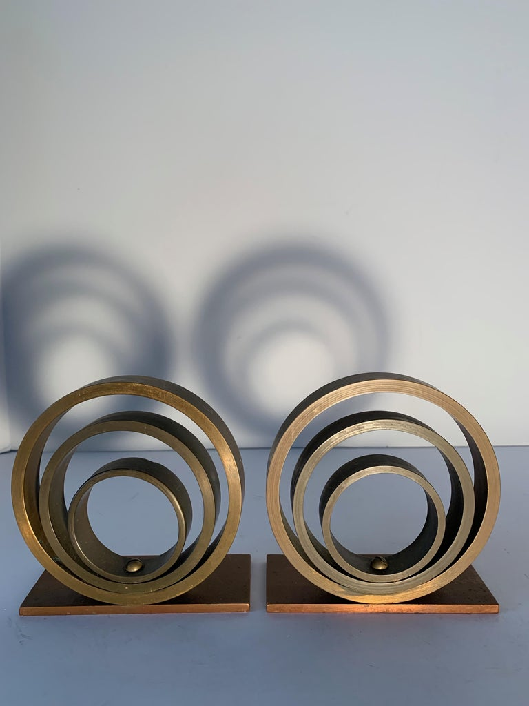 Pair of brass and copper ring bookends in the manner of Walter Von Nessen. Architectural, Industrial, Art Deco, simplicity defined elegance.  Perfect for any shelf, in any space in your home - statement pieces for the sophisticated.