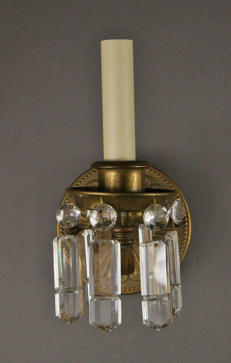 2-401, pair of brass and crystal one arm sconces. Takes one 60 watt max candelabra base bulb.