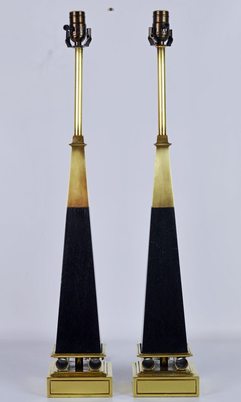 These Mid-Century Modern table lamps in the shape of obelisks represent an iconic Tommi Parzinger design. They feature solid brass top sections above ebonized wood columns resting on a square solid brass base intersected by classical inspired brass