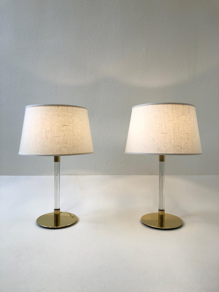 """A beautiful pair of polish brass and clear glass table lamps design by Hansen Lamps New York and made in Spain by Metalarte. The lamps show minor wear consistent with age (see detail photos). New vanilla linen shades. Measurements: 16.25"""""""