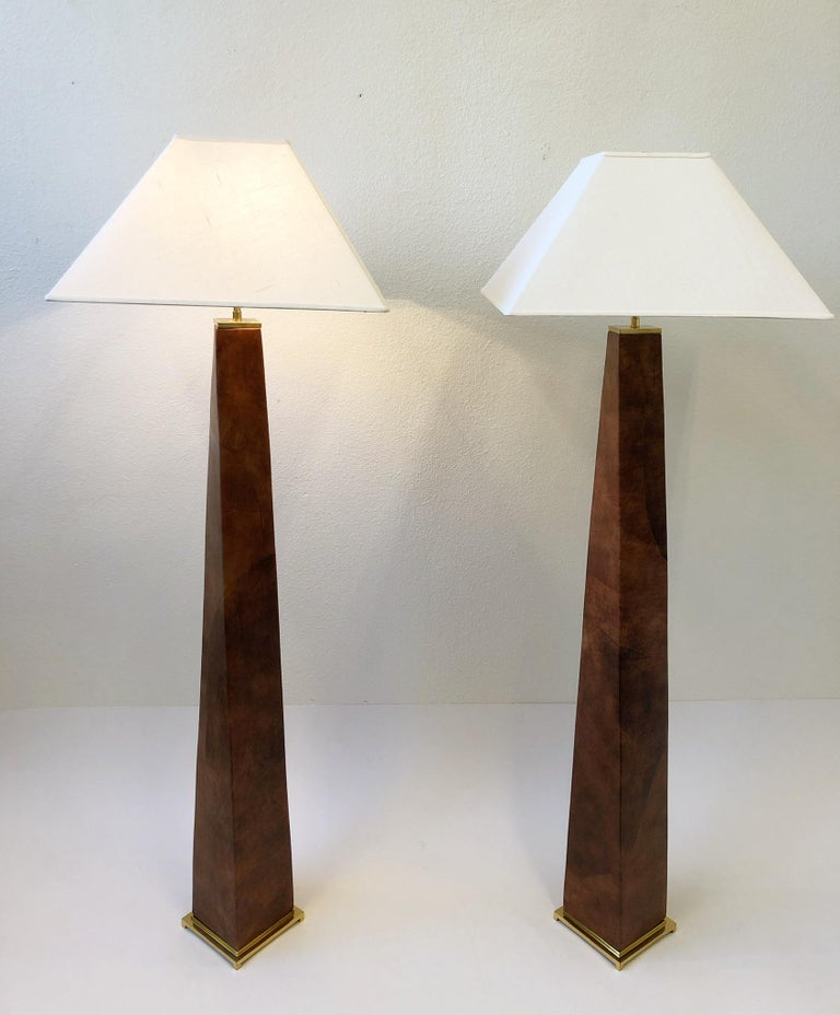 A spectacular pair of 1980's polish brass and leather J.M.F. floor lamps by renowned American designer Karl Springer. The lamps are constructed of solid brass and wood that's covered In a patchwork saddle tan leather. New rewired and new vanilla