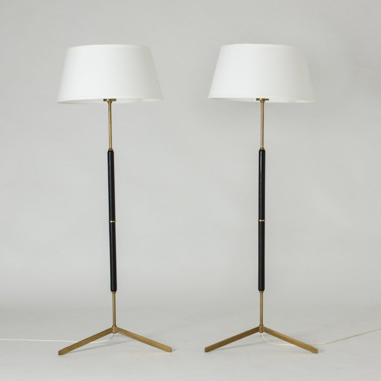 Pair of sleek and cool floor lamps from Bergboms, made from brass and black lacquered wood. Tiltable lamp shades, nice brass hoops around the light bulbs make a decorative detail inside.