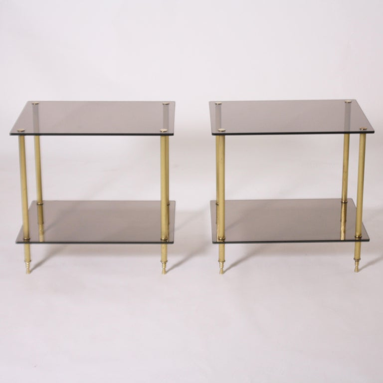 Pair of brass and smoked glass tables, circa 1950.