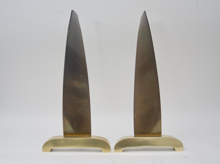 This stylish and chic set of brass andirons are by the Mid-Century Modern designer Donald Deskey and they date to the 1950s. Here Deskey has put a modern twist with a stylized flame-form and the piece is in a satin and antique finish.  Note: The