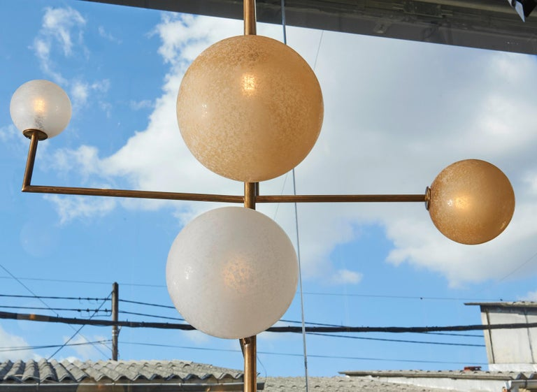 Pair of chandeliers made of a brass geometrical structure and frosted white and yellow globes.