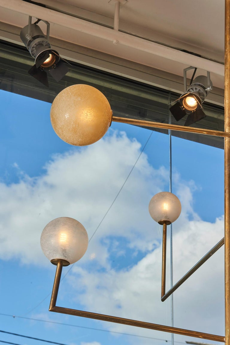 Contemporary Pair of Brass Angular Chandeliers with Glass Globes For Sale