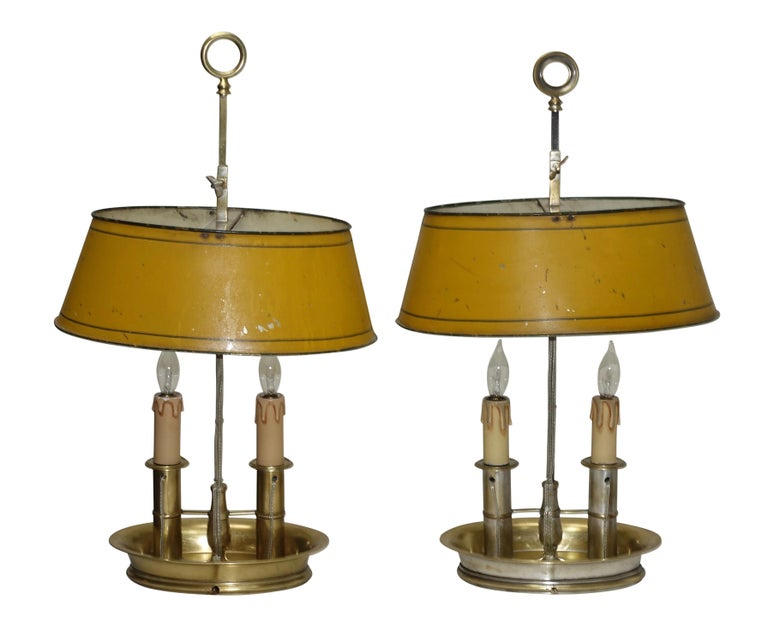 A charming pair of brass bouilotte lamps with mustard yellow tole' shades with a green pinstripe around the top and bottom of the shade. One of the lamps has remnants of silver plating. Two sockets up in the shade and two sockets in the