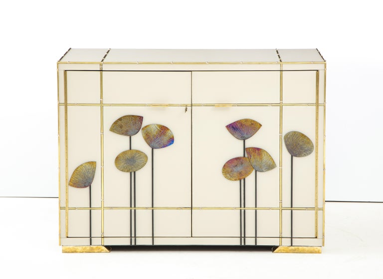 One of a kind pair of sideboards handmade in Venice, Italy by a master artisan and artist. Wooden frame is covered in ivory hand tinted Murano glass panels with faux bamboo brass inlays. Handcut iridescent gold glass Dandelions in a Classic