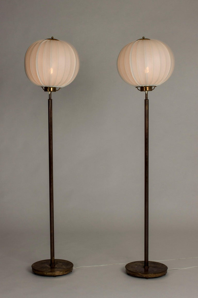 Pair of amazing floor lamps by Bertil Brisborg, made from brass. Great, dark patina. Voluminous shades that spread beautiful light. Very elegant proportions.