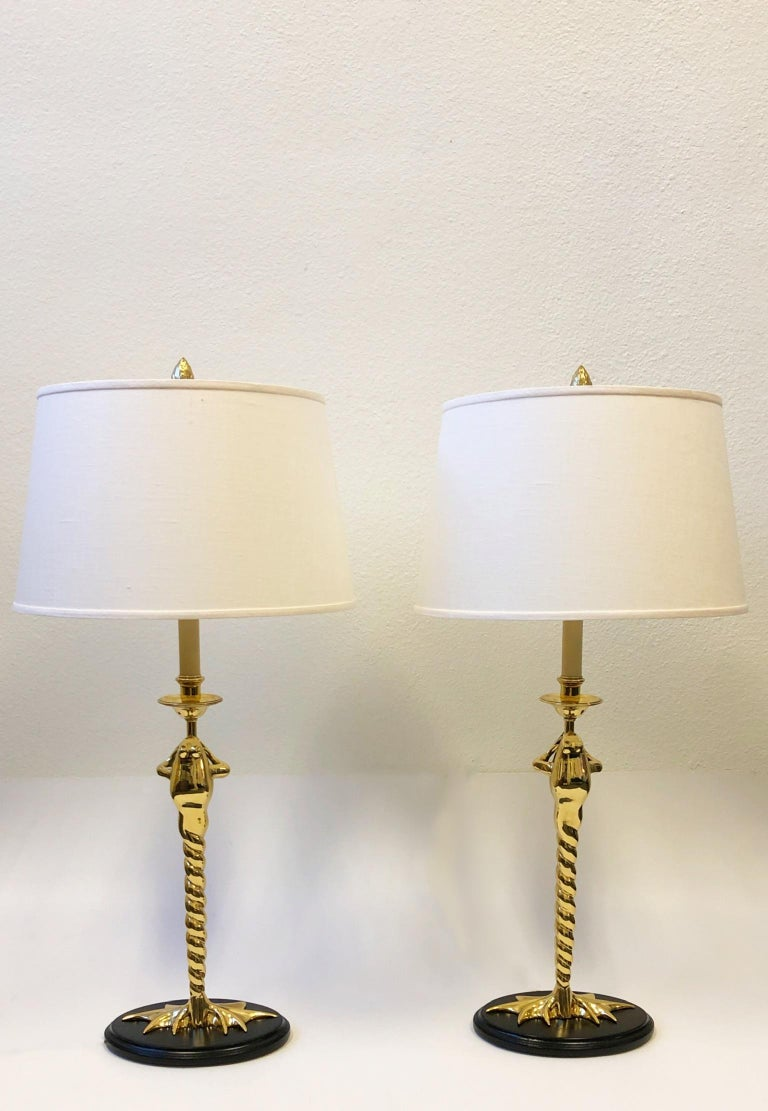 """A glamorous 1970s pair of polished brass and black lacquered frog table lamps by Chapman lighting. The lamps have been newly rewired and new vanilla linen shades. Measurements: 16.5"""" diameter, 32.25"""" high to top of shade. Base is 9.5"""" wide, 6.75"""""""