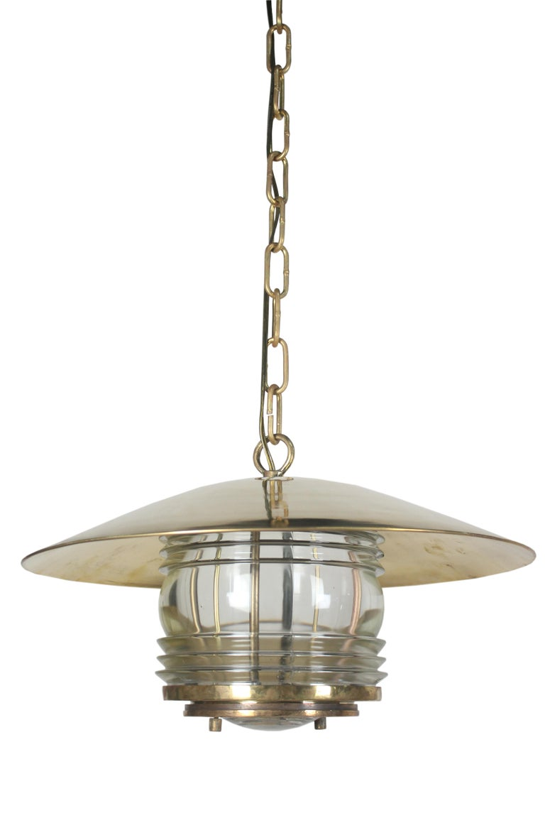 A pair of brass ship's lights with Fresnel Lens glass. These were originally post lights converted to hanging pendant chandelier lights. Circa 1970's from a decommissioned ship. Originally European, rewired for American use. The plate underneath