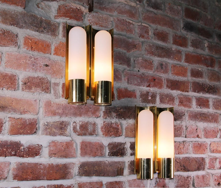 One pair of wall lights with brass and opaline glass elements. Made in the 1970s by Glashuette Limburg, Germany. Measures: Width (each) 20 cm / 7.87 in., height 33 cm / 13 in, depth 9 cm/ 3.5 in. Each lamp takes two small Edison bulbs.   8 sets in