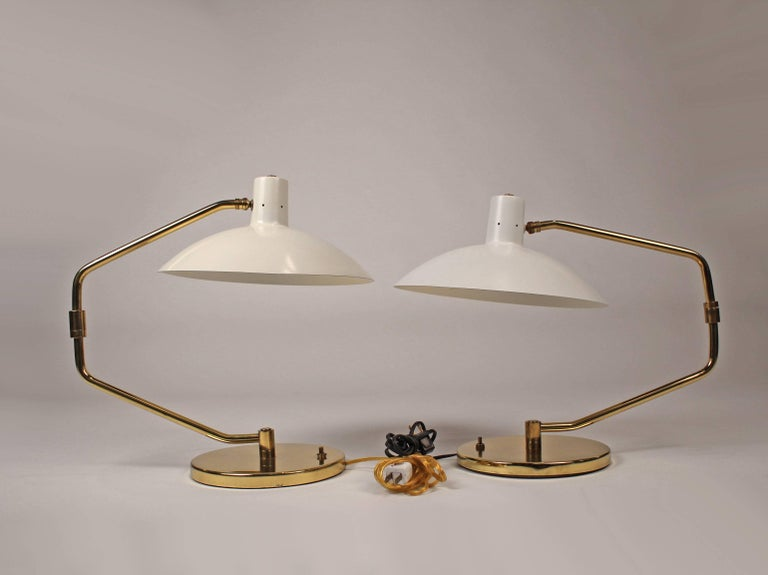 A pair of table lamps featuring adjustable shades with pivoting arms that extend to a length of 33 inches. One lamp is slightly older than the other so they are not a 100% match but indistinguishable when separated in a room. They would make amazing