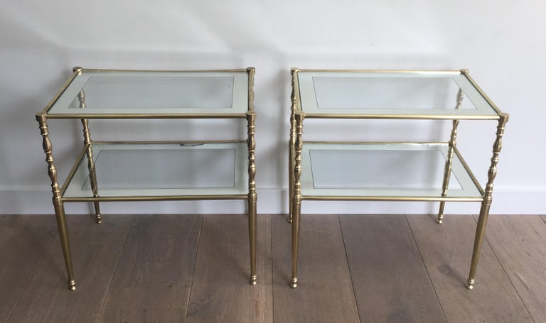 This very elegant pair of side tables is made of brass with clear glass shelves surrounded by a silvered mirror. line French, circa 1970.