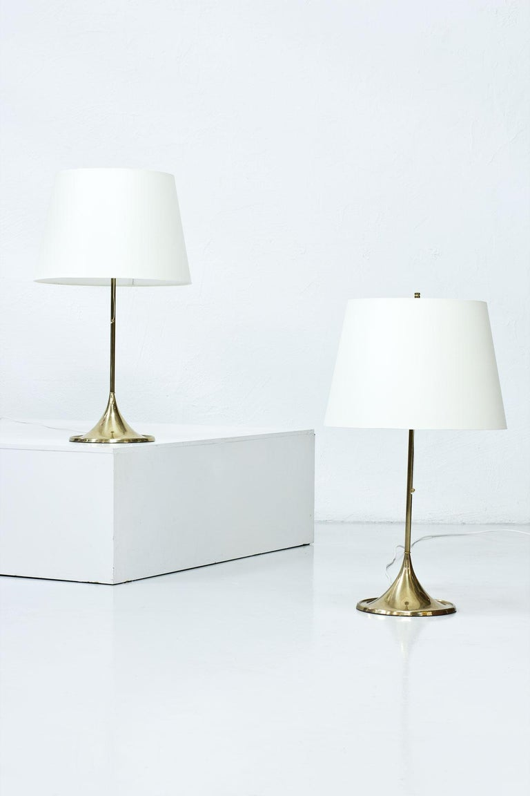 Pair of table lamps model B-024 designed by Alf Svensson and Yngvar Sandström, (Studio S-Design) manufactured by Bergboms in Sweden during the 1960s.  Polished brass stem, cast iron base, acrylic top diffuser and shades newly redone (handmade in