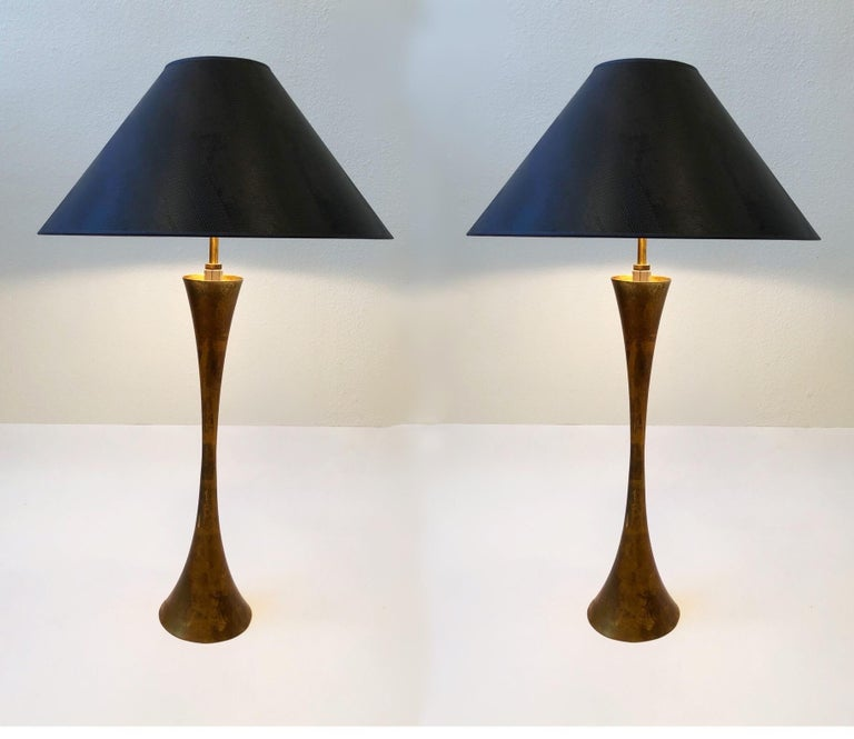 A beautiful pair of brass hourglass shape table lamps designed by Stewart Ross James for Hansen Lighting Co. in the 1950s. The lamps are constructed of solid brass that's gold leaf gilded. Newly rewired with original three way rotating switch. New