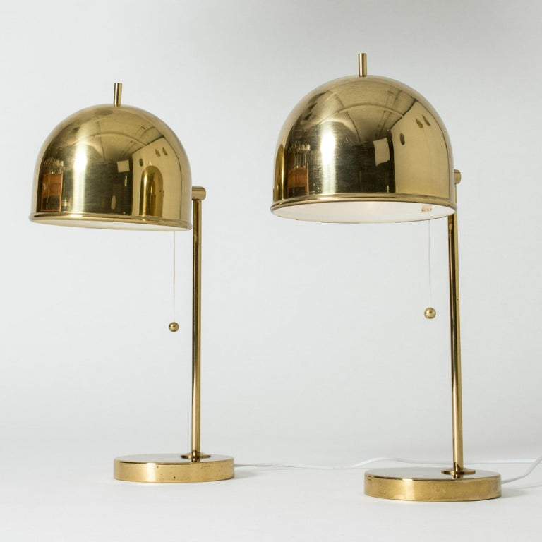 Pair of brass table lamps from Bergboms in a design that combines the generous arches of the shades with strict lines. The little tips on the tops of the shades add a whimsical look.