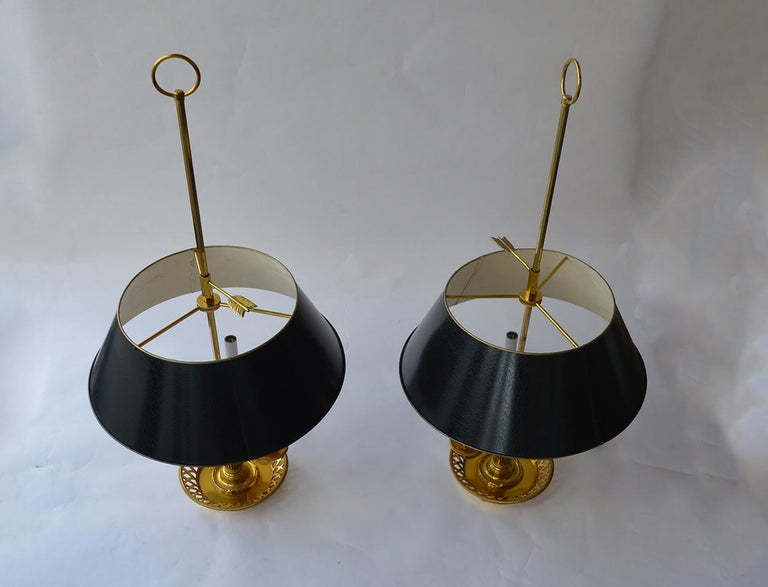 Two brass lamps with painted tole lampshades.