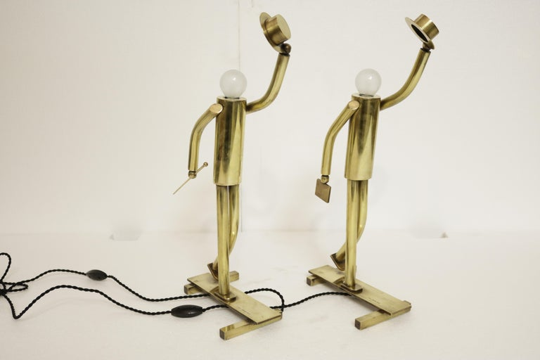 Unique pair of high-end brass lamps in the form of sphere bulb-headed figurines sporting top hats and cane or suitcase. The words