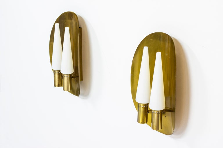 Pair of wall lamps designed by Hans-Agne Jakobsson. Produced by Hans-Agne Jakobsson AB in Sweden, during the 1960s-1970s. Made from solid brass with four conical opaline glass shades. Both lamps signed with label. Very good vintage condition with
