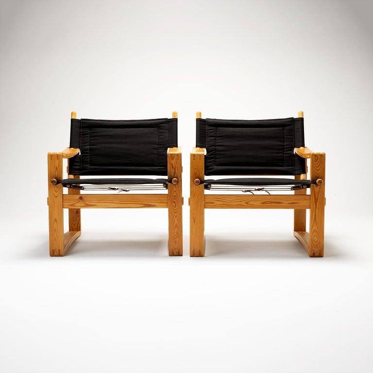 A pair of pine safari chairs designed by Børge Jensen for Bernstorffsminde Møbelfabrik, Denmark. New black canvas upholstery. Excellent vintage condition.